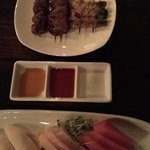 Sashimi and bento box and skewers of chicken hearts and beef tongue and bacon wrapped over aspar