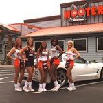 Hooters girls pose in front of restaurant