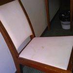 Detalle de la suciedad de la única silla de la habitación y de la pared