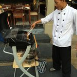 Wayan warming up the BBQ for pork ribs and corn