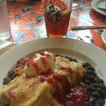 Chicken & chorizo enchiladas over spiced black beans w/ sour cream & berry jalapeño purée