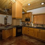 """Homestead """"4 Seasons"""" downstairs kitchen with counter top bar and dining area."""