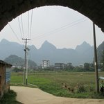 Looking out from an arched doorway in village Jiuxian accross the fields towards a few peaks