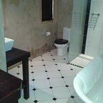 Banheiro com chuveiro, banheira e produtos de primeira
