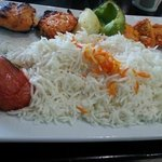 Salmon kabob entree, with rice and wedges of tomato, onion and bell pepper.