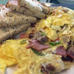 Beachside Skillet Eggs, Ham, Bacon, Sausage, Onion, Green Pepper, Tomatoes & Hash Browns are Gri
