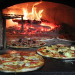 pizzas in wood fire oven