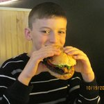 Our grandson eating a bacon burger at Marbles