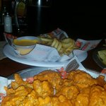 Boneless hot buffalo wings, curly fries and chesse sauce. Wings could of been covered in sauce b