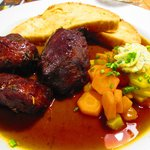 Delicious pork cheeks with vegetables and pretzel bread