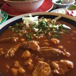 Pozole pork soup with Birria goat stew in background