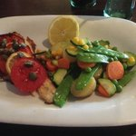 Oven-baked fillet of sea-bass with sliced tomatoes, capers and lemon juice