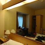 Quarto bem iluminado, espelho grande