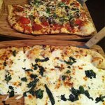 Foreground - white pizza as listed on menu  Background- create your own- pepperoni, mushroom, an