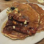 Two blueberry pancakes with three bacon rashers