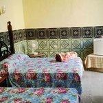 Amplia habitación con dos camas matrimoniales, minibar, baño privado.