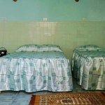 Habitación con una cama camera y otra personal. Baño privado con agua fría y caliente.