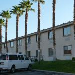 le bâtiment comprenant les chambres avec le parking juste devant.