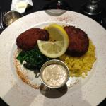 The crab cakes with sauteed spinach and yellow rice, side sauce