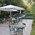 Tables and chairs in the garden with heaters under umbrellas