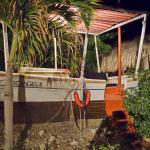 Peñero dentro del hotel con muebles dentro para sentarse en el. Little boat in the swiming pool