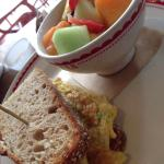 Egg and tomato sandwich with multi grain bread and a bowl of fruits