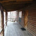 Cabin porch with porch swing and cabin entrance.