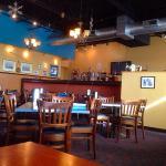 Dining area toward bar behind wall.