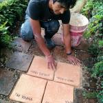 Bolom placing tiles for donors