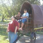 The front of the buggy. Cashea acting as a horse with Nojah and Nikolas holding the reins.