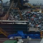Equipment loading scrap onto conveyor belt at LOUD metal scrap yard next to hotel