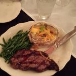 New York steak with baked potato and green beans.