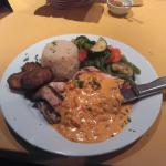 Frango Gelhado. Grilled chicken topped with sundried tomato sauce, fried plantains, rice and veg