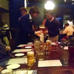 """Dinner guest shares his """"boot"""" of beer."""