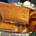 Full-size pressed Cuban sandwich (onion rings ordered as a side).