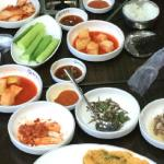 Spread of side dishes and 2 pots of different soup