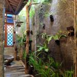 Beautiful semi-outdoor bathroom with stone bath and rainforest shower