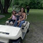 Cedar Ridge grandkids driving gulf cart.