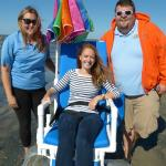 Staff with guest using beach wheelchair (provided by Resort)
