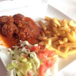 Creole meatballs with fries and a small salad.