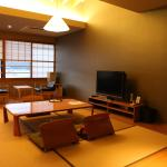 tatami style living room with easy chairs by the window and large flat-screen TV