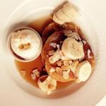 Pancakes with banana, flaked almonds and maple syrup.