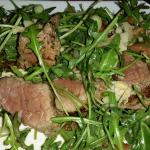 Beef on a bed of pesto with rocket.