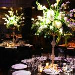 Dramatic grand floral centerpieces adorn tables and purple lighting creates ambiance