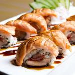 Yakan Uramaki - uramaki de tomate seco coberto por sashimi de salmão maçaricado.