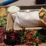 Wild salmon in pita with sides of hummus, peas, beets, tabouli, slaw