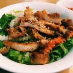 Grilled pork strips and fried springrolls on a bed of dry Vietnamese vermicelli  noodles and veg