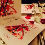 Menu and rose petals on table