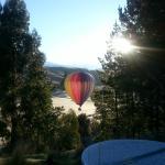 hot air balloon sails below the spa pool