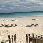 Private beach access with chairs and umbrellas for guests